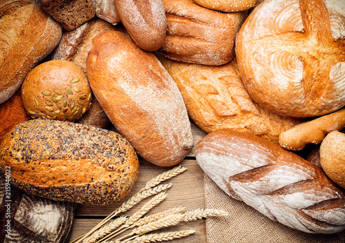 Foto Murales heap of fresh baked bread on wooden background