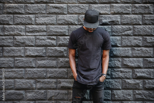 Handsome african american man in blank black t-shirt standing against brick wall - 215946439