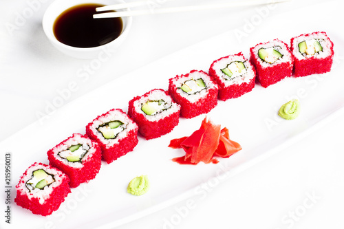 Canvas Sushi bar Japanese sushi rolls with avocado in red caviar of flying fish on white plate