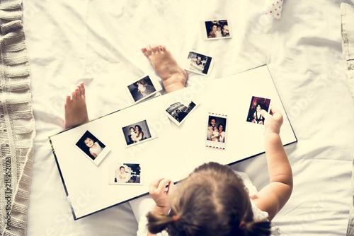 Foto Murales Little girl looking her family photo in album
