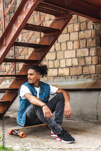 Foto Murales stylish mixed race man sitting on skateboard at urban street