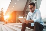 Portrait of businessman in glasses holding tablet - 215964640