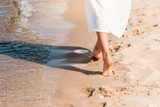partial view of barefoot girl in white dress walking on sandy beach near water