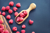 Fresh organic raspberries on black background. berries on a wooden spoon.