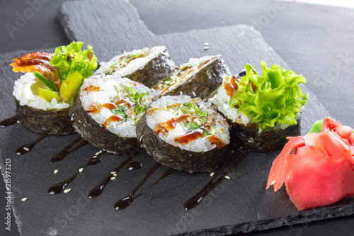 Foto Spatwand Sushi bar Japanese restaurant, sushi roll on black slate plate.