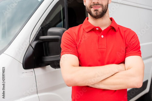 Foto Murales cropped shot of delivery man in red uniform with arms crossed standing at van