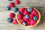 Raspberries and blueberries in a basket on a wooden table.
