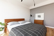 Leinwandbild Motiv Patterned grey blanket on wooden bed in hotel bedroom interior with poster above cabinet. Real photo