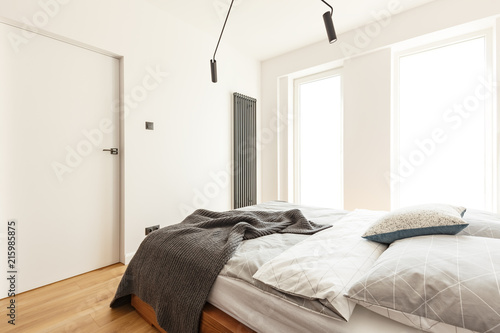 Pillows and blanket on bed in white bedroom interior with windows and door. Real photo