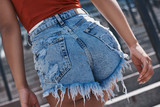 Young woman in jeans shorts free style on the street walking up  - 216003885