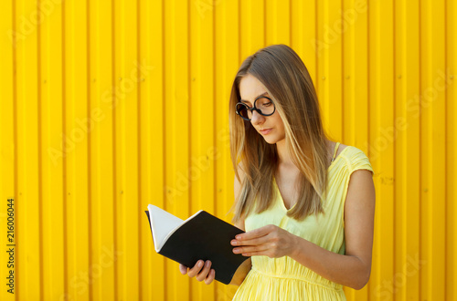 Pretty smiley girl student with book wearing funny toy round glasses