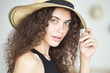 Fashion portrait of young brunette woman with no makeup wearing straw hat, shallow depth of field