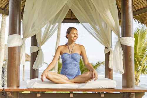Sticker An Asian young woman is making yoga near swimming pool near the beach on Bali