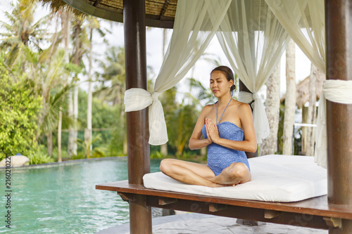 Fototapeta An Asian young woman is making yoga near swimming pool near the beach on Bali