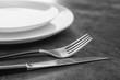 Leinwandbild Motiv Empty dishware and cutlery on gray background, close up view. Table setting