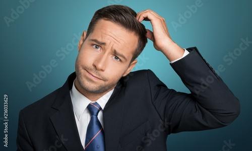 Leinwandbild Motiv Young businessman scratching his head, hard decision