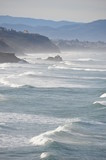 Les vagues de l'océan atlantique se brisent sur la côte basque, les Pyrénées sont visibles dans le lointain