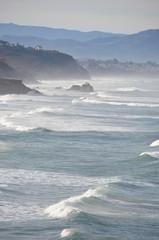 Les vagues de l'océan atlantique se brisent sur la côte basque, les Pyrénées sont visibles dans le lointain © hubert