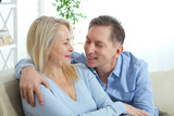 Middle aged couple relaxing on the couch smiling at camera at home in the living room - 216034625