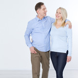 Full length portrait of happy mature couple standing with hands in pockets over white background - 216034845