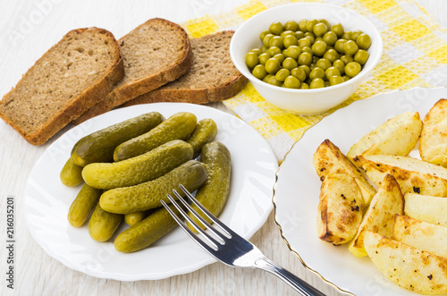 Fried pieces of potato, bread, gherkins, green peas, fork © Evgeny