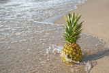 pineapple on sandy beach with splashing water