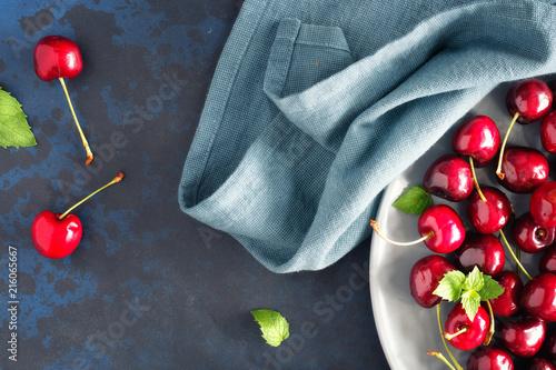 Foto Spatwand Kersen Top view on the gray plate of cherries on dark background