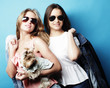 Quadro lifestyle and people concept: Two young girl friends standing together and holding dog