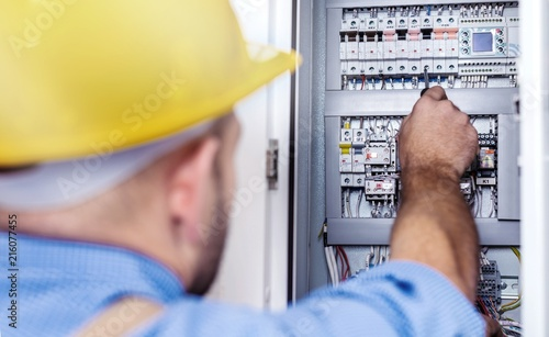 Leinwandbild Motiv Hand of an electrician with multimeter probe