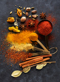 Spices and seasonings in measuring spoons and on a table - 216081805
