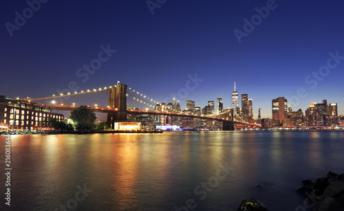 Foto Spatwand Brooklyn Bridge Panorama of Brooklyn Bridge and New York City (Lower Manhattan) with lights and reflections at dusk, USA