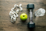 Fitness and health concept : Green apple ,dumbell, bottle of water and measuring tape  on the  wooden table. - 216089807