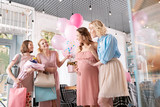 Pink dresses. Two stylish women wearing pink dresses coming to baby shower in nice modern bakery