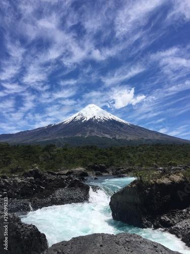 Foto Spatwand Zwart Wildwasser-Fluß vor Schneebedecktem Vulkan