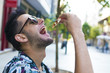 young eating portion of outdoor pizza in the city