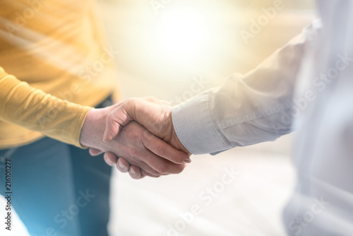 Woman and man shaking hands in office, light effect
