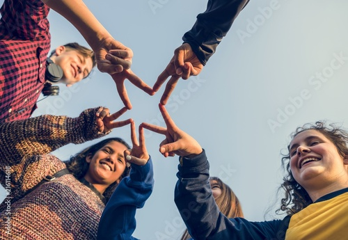 Leinwanddruck Bild Group of friends using fingers to form the star shape teamwork and support concept