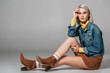 Quadro beautiful model in trendy corduroy skirt and jeans jacket sitting on floor, on grey