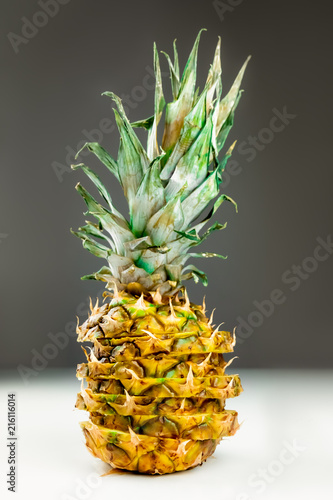 Close-up of sliced pineapple on white and grey background. Front view of creatively cut  ripe fresh pineapple - 216116014