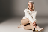 smiling elegant model posing in white sweater, beige pants and autumn heels, on grey - 216118037