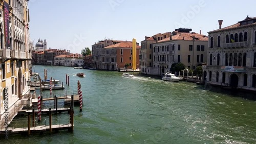 Going to the right and up a bridge in Venice. Boats in the river. Sunny weather.