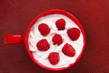 Yoghurt with raspberries on red texture