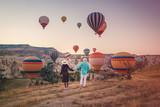 happy young couple during sunrise watching the hot air balloons of Kapadokya Cappadocia Turkey - 216125613