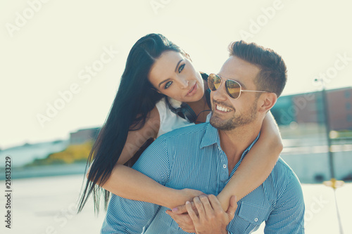 Happy young woman piggyback ride man outdoors in sunset
