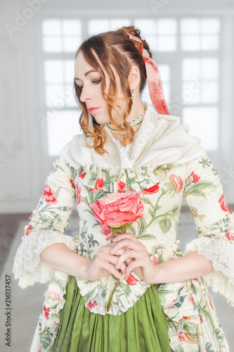 Beautiful woman in green medieval dress with flower