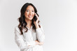 Leinwandbild Motiv Image closeup of attractive chinese woman with long dark hair holding smartphone and having mobile call, isolated over white background in studio