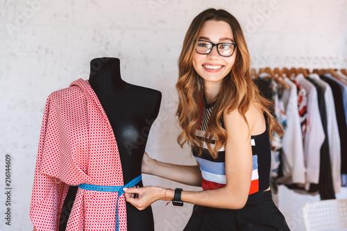 Leinwandbild Motiv Positive young woman clothes designer at the atelier