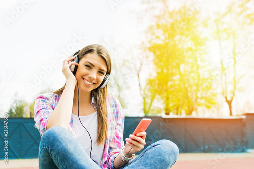 Foto Spatwand Muziek Happy teenage girl listening to music outdoors with headphones and smartphone. Natural lighting, closeup, vibrant colors.