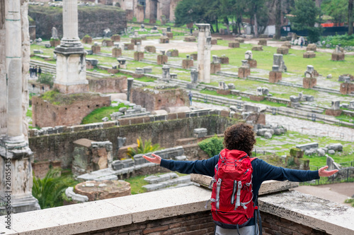 Foto Murales Young backpacker looking at Roman forum in Rome
