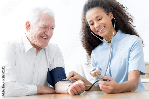 Foto Murales Smiling doctor with stethoscope examining happy elderly man in the hospital